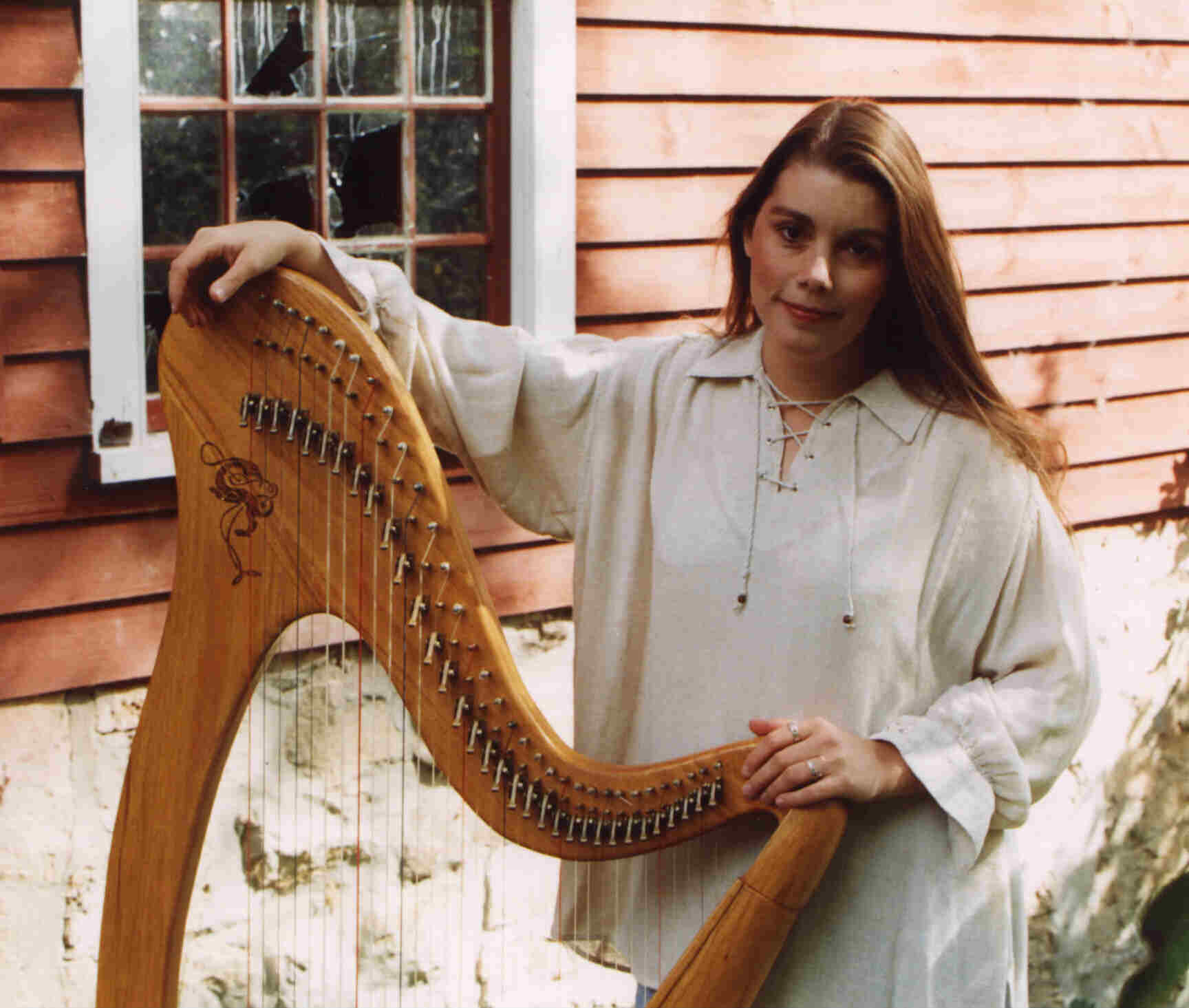 Jennifer and her harp, in front a window of the old mill in Otterville, Ontario, Canada